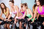 Attraente femmine sulle biciclette in un fitness club — Foto Stock