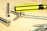 Screw-driver screws on a board — Stock Photo