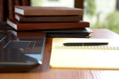 Organizers the laptop writing-book and pen on a desk — Stock Photo