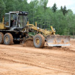 Stock Photo: Grader clears away