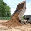 Dump-body truck unloads a ground — Stock Photo