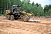 The grader clears away — Stock Photo