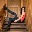 Girl sits on a wooden ladder — Stockfoto