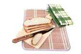 Slices of bread with knife chopping board and towel — Stock Photo
