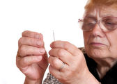 The old woman passes thread in needle — Stock Photo