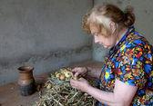 Yaşlı kadın bir soğan kendini keser — Stok fotoğraf