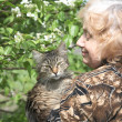 Royalty-Free Stock Photo: The old woman holds on hands of a cat against