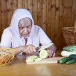 The old woman cuts  vegetable marrow - Stock Photo