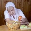 The old woman touches onions sitting — Stock Photo
