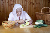 The old woman cuts vegetable marrow — Stock Photo
