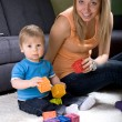 Stock Photo: Young mother playing with baby boy