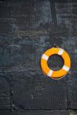 Lifebuoy on a black wall — Stock Photo
