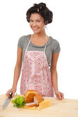 Beautiful cooking woman in apron with sandwich. — Stock Photo