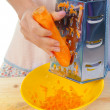 Hand holding carrot vegetable  grater - Stock Photo