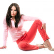 Beautiful young brunette in red jeans — Stock Photo