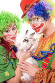 Two smiling clown with a white rabbit — Stock Photo