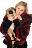 Beautiful blonde holding a pekinese — Stock Photo