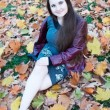Stock Photo: Girl sits on autumn leaves.