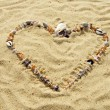 Heart from cockleshells and sea pebbles — Stockfoto