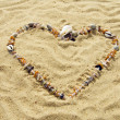 Heart from cockleshells and sea pebbles — ストック写真