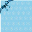 Snowflakes blue background with blue ribbon and bow. Place for c - Zdjcie stockowe