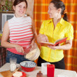 Stock Photo: Women making Easter cake with cookbook