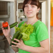 Woman putting fresh vegetables   into refrigerator - Stockfoto