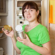Woman putting with metal can near refrigerator - Stock Photo