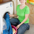 Woman putting clothes into washing machine - Foto Stock