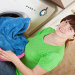 Woman putting clothes in to washing machine - Foto Stock