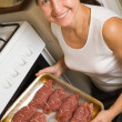 Woman putting stuffed beef  into oven - Stok fotoraf