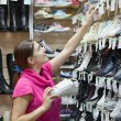 Girl chooses shoes at shoes shop — Stock Photo