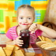 Girl eating jam from jar — Stock Photo