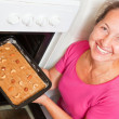Woman putting dough  into oven - Stok fotoraf