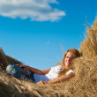 Girl resting on fresh straw — Stock Photo