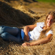 Girl resting on fresh hay - Stock Photo