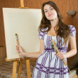 Girl with brush near easel — Stock Photo
