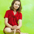 Sitting girl in red dress — Stock Photo