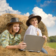 Country girls  in cowboy hat  with laptop — Stock Photo