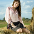 Pretty girl on straw bale — Stok fotoğraf