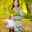 Girl with maple leaves in park — Stock Photo #5432351