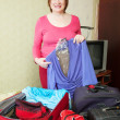 Mature woman packing suitcases — Stock Photo #5434636