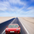 Red car on desert road — Stock Photo