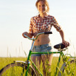 Girl with bicycle in grass — Stock Photo