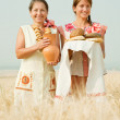 Women with bread at cereals field — Stock Photo