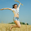 Jumping girl with wheat ears — Stock Photo