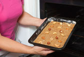 Female hands puts dough into oven — Stock Photo