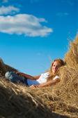 Girl resting on fresh straw — Stock Photo