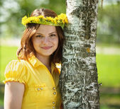 Girl in flowers wreath near birch — Stock fotografie