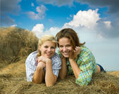 Girls on hay in summer — Stock Photo